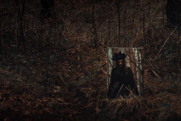 우울한 숲에서 거울에 어두운 무서운 마녀의 반영