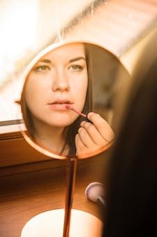 Отражение женщины, применяющей помаду на губах