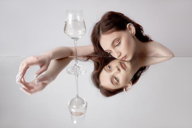 Отражение женщины в зеркале со стеклом в руке.