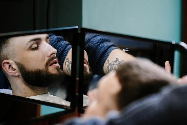 美容師の鏡でひげのある男の反射