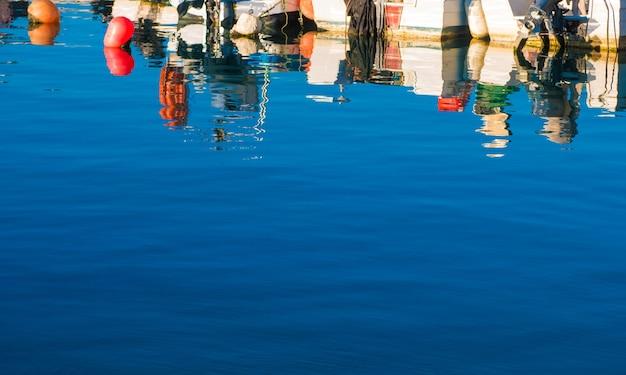 Отражение лодок, стоящих на пирсе фарос.