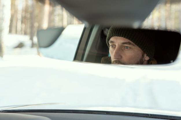 カントリーハウスや他の場所に運転中に車のフロントウィンドウを通して見ているウィンターウェアの若いアクティブな男の顔の反射