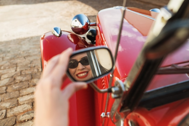 古い赤い車の幸せなドライバーの中に座っている女の子の反射
