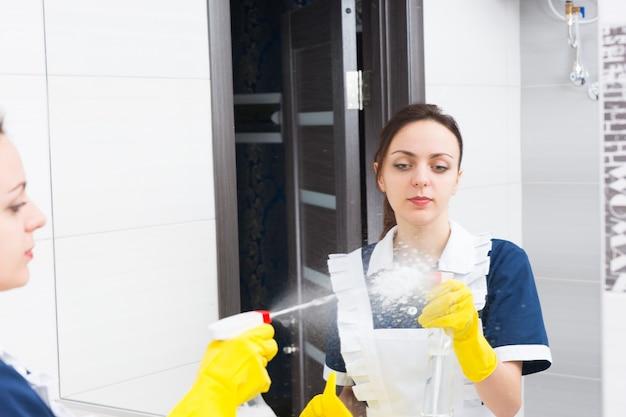 Отражение серьезной молодой взрослой горничной, брызгающей стеклоочистителем на зеркало во время работы в ванной комнате отеля