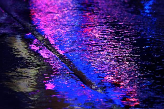 Отражение рекламных огней на камнях дороги под дождем