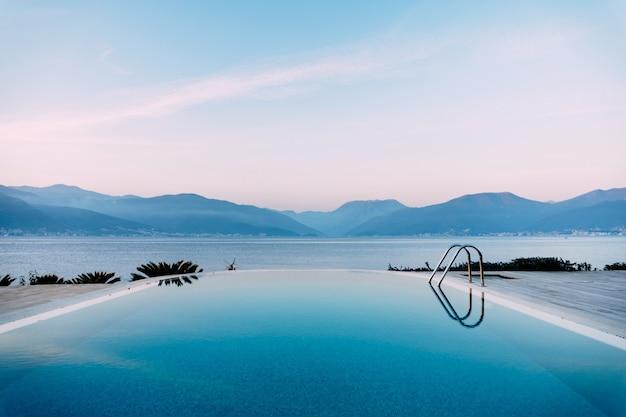 海の近くのプールの滑らかな水の中の夕方の空の反射を背景に