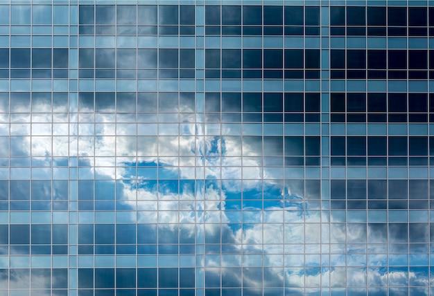 複数階建てのガラス建物の窓にある空と雲の反射。