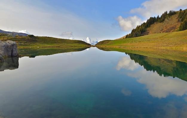 고산 산 호수의 물에 하늘과 나무의 반사