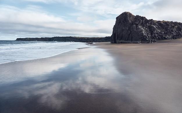 파도에 젖은 해변의 모래에 하늘의 반사