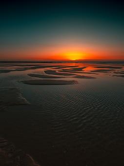 オランダ、ドンブルグで撮影された海の夕日の反射