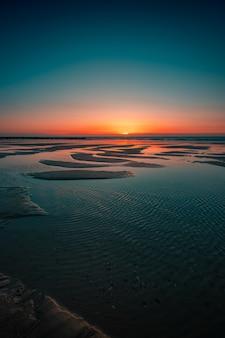 オランダ、ドンブルグの海に沈む夕日の反射
