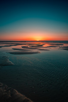 Domburg, 네덜란드에서 바다에 일몰의 반영