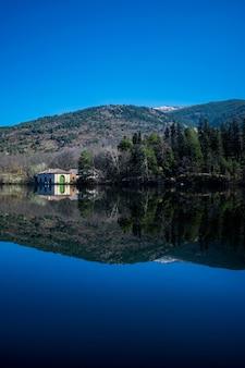 日光と青い空の下で湖の樹木や丘の反射