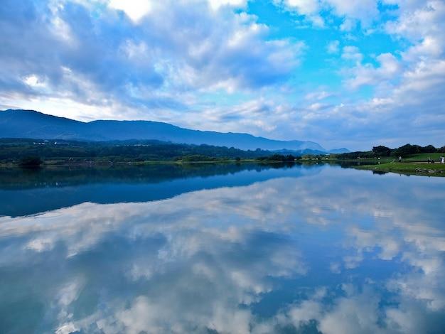 Отражение деревьев, гор и островов на чистом озере