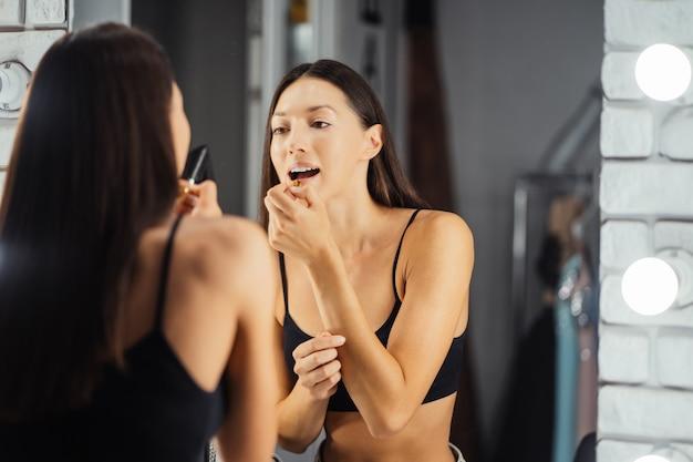 彼女の化粧を適用している若い美しい女性の反射