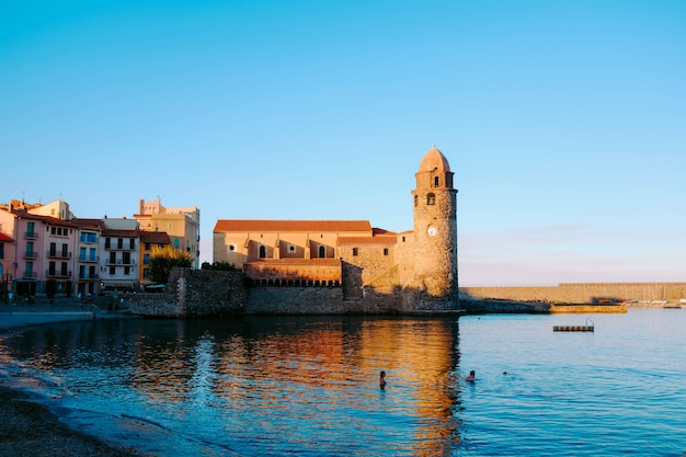 Reflection of an old castle in the calm water of the sea under the blue sky