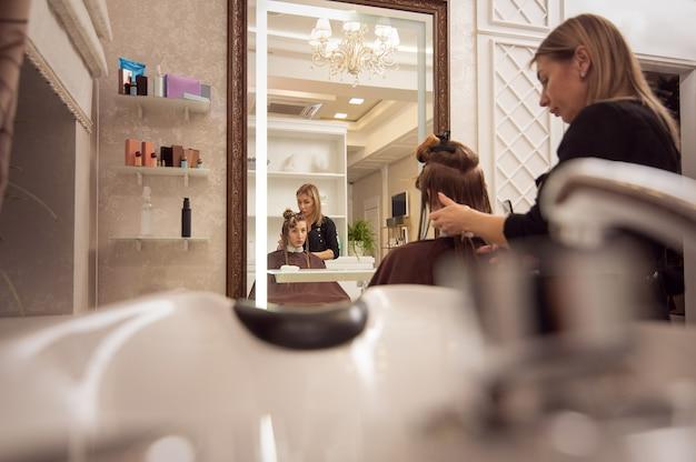 ビューティーサロンで大人のエレガントな美容師によって散髪されている若い女性の鏡に映る