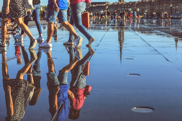 Reflection of people walking on bordeaux water mirorr, france