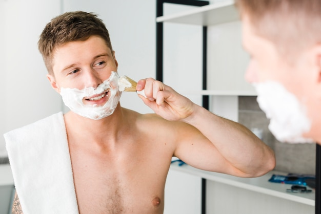 Reflection of shirtless young man with white towel over his shoulder shaving with brush