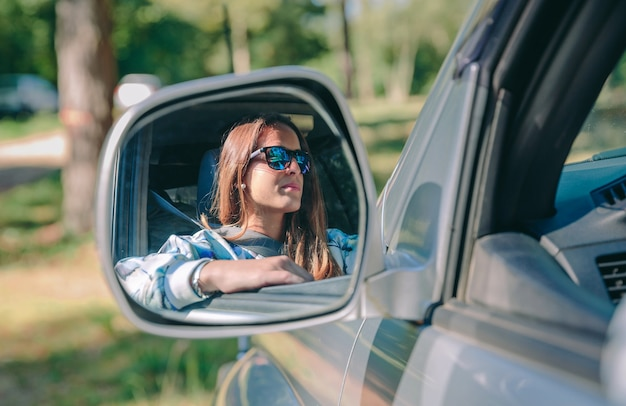Reflection in side view mirror of young woman with sunglasses driving car over a nature background