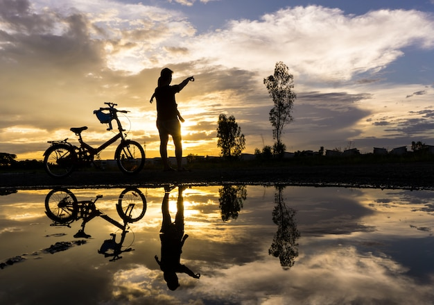 Reflection silhouette of mother with her toddler against the sunset.