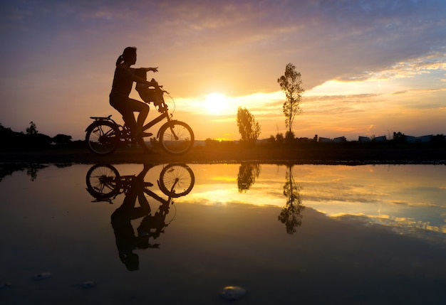 Reflection silhouette of mother with her toddler on bicycle against the sunset and lens flare.