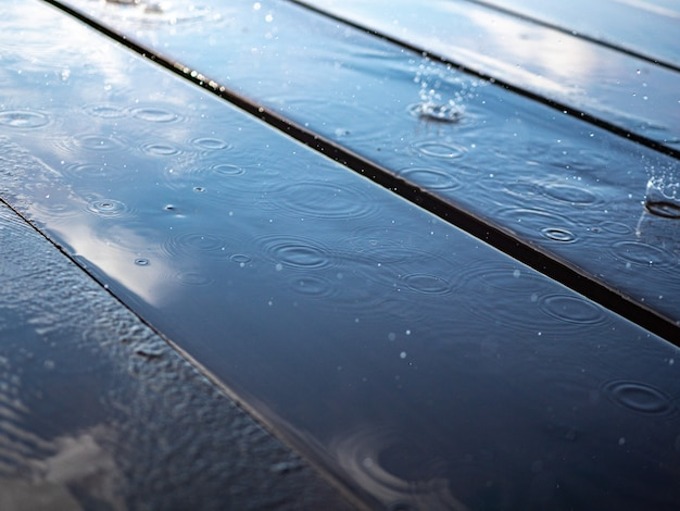 Reflection of the sky in a puddle on wooden boards