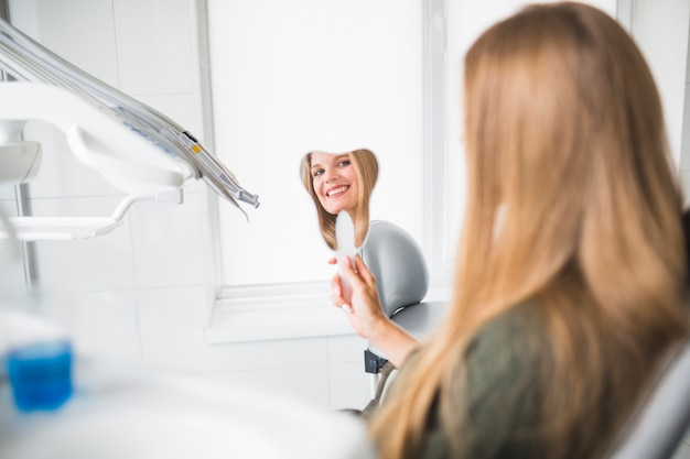 Reflection of smiling young woman in hand mirror at clinic