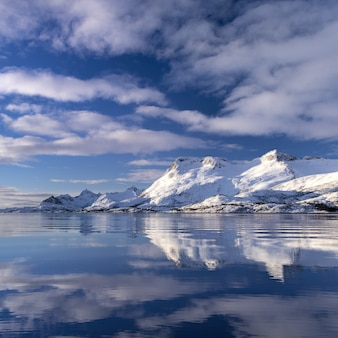 Reflection of a snow covered cliff in the water under the beautiful clouds in the sky in norway