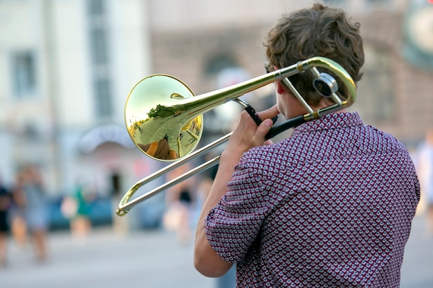 Reflection of the street in the instrument solo trumpet. male musician plays the trombone.