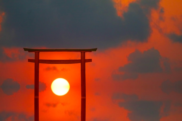 Reflection torii sunset red gray cloud on the sky over the sea
