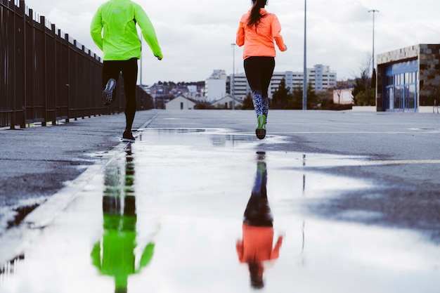 Reflection of two athletes running on street in a puddle