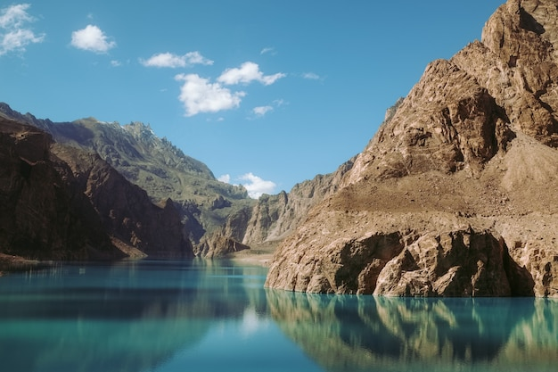 Reflection in the water of attabad lake, surrounded by mountains in karakoram range.