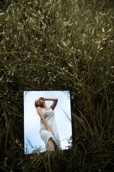 Reflection of a woman in a dress in a mirror in the grass