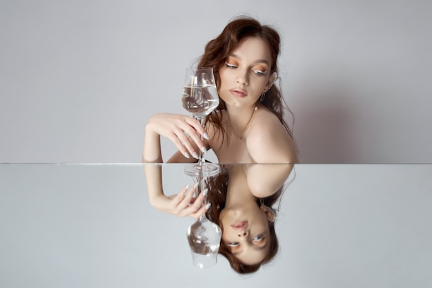 Reflection of a woman in mirror with glass in her hand. beautiful face makeup, natural cosmetics