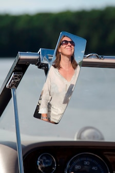 Reflection of a woman on the rear view mirror on a motor boat, lake of the woods, ontario, canada