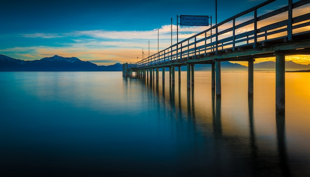 Reflection of a wooden pier on the sea with the mountains and the sunrise