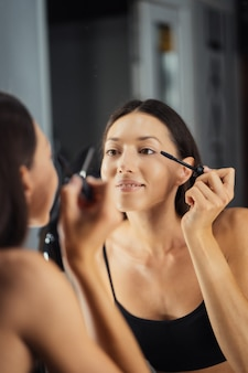 Riflessione della giovane bella donna che si trucca, guardandosi allo specchio