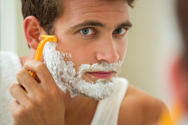 Reflection of young man shaving