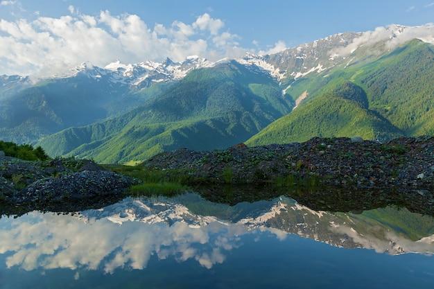 Отражения в воде пейзажа с горными снежными вершинами летом возле села местия