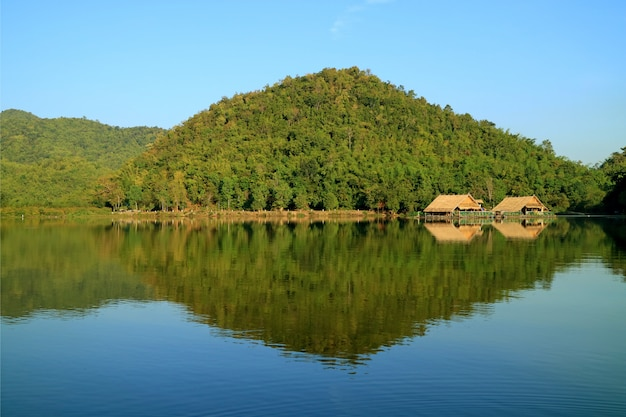 Reflections of mountains and the rafts on hoob khao wong reservoir, thailand