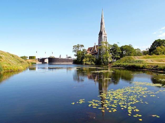 コペンハーゲン、デンマークのkastellet(シタデル)の池に聖アルバン教会の反射