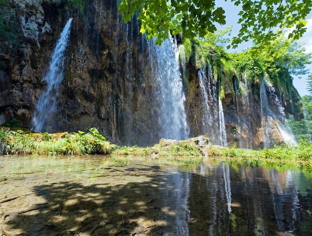 小さな純粋な透明な湖(クロアチア、プリトヴィツェ湖群国立公園)の滝の反射