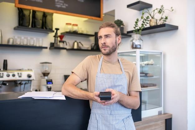 반사. 바 카운터 근처 카페에 서있는 그의 손에 pos 터미널을 가진 심각한 젊은 수염 난된 남자 생각