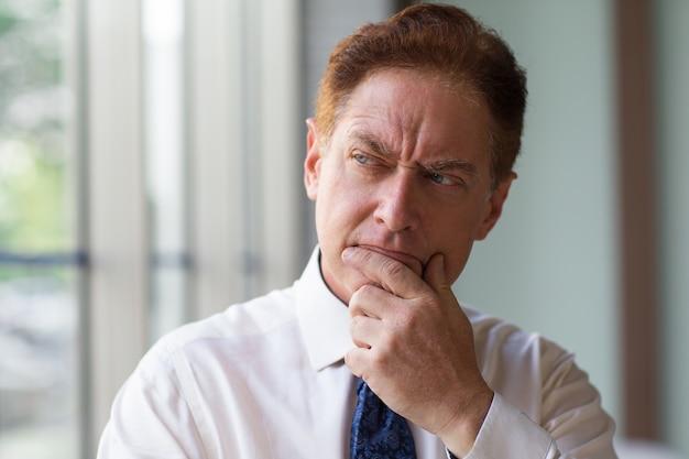 Светоотражающий мужчина-генеральный директор, потирающий подбородок, когда он думает
