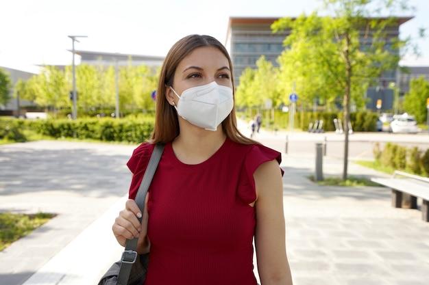 측면을 바라보는 보호 마스크를 쓰고 빈 도시 거리에 반사 젊은 여성