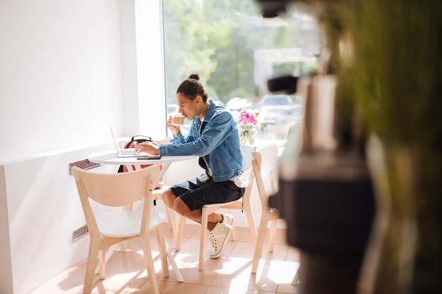 リフレッシュしてください。おいしいコーヒーを飲み、コンピューターで働く真面目な男性