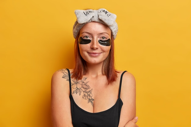 Освеженная женщина, одетая в черную футболку, мягкую повязку на голову, накладывает коллагеновые пластыри для уменьшения отечности и темных кругов, ухаживает за кожей вокруг глаз. концепция ухода за лицом. утренняя рутина