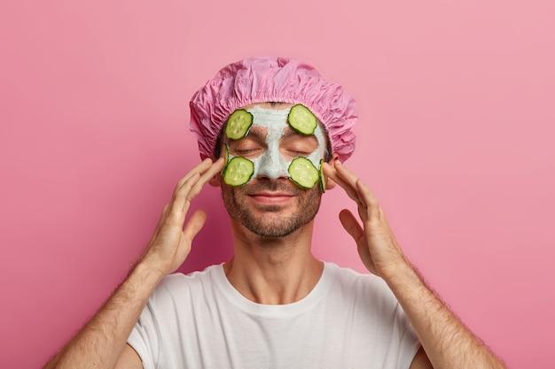 상쾌한 기뻐하는 남자가 뺨을 만지고, 얼굴에 오이 슬라이스와 클레이 마스크를 바르고, 부드럽고 깨끗한 피부를 원하고, 목욕 캡을 쓰고, 샤워를합니다.