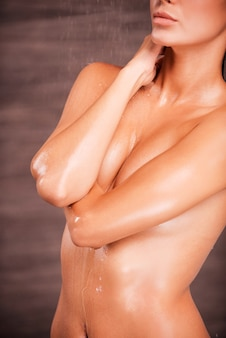 Refreshed and revitalized. beautiful young naked woman standing in shower and covering breasts with hands